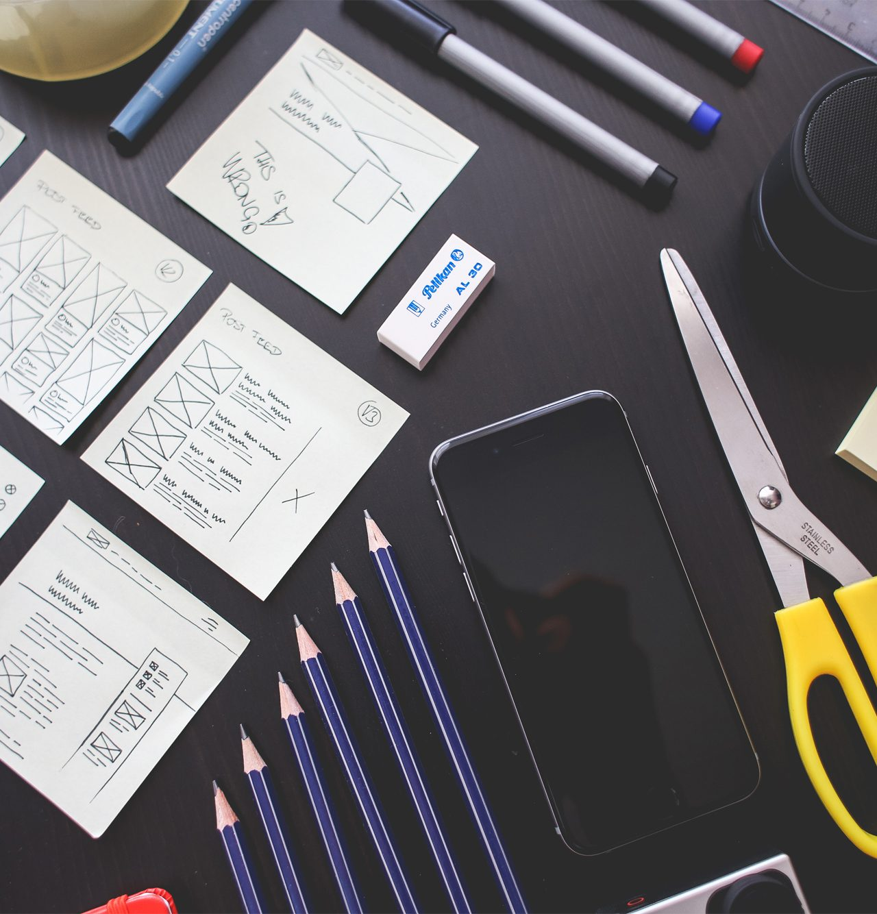 design wireframes laid out on a table with supplies